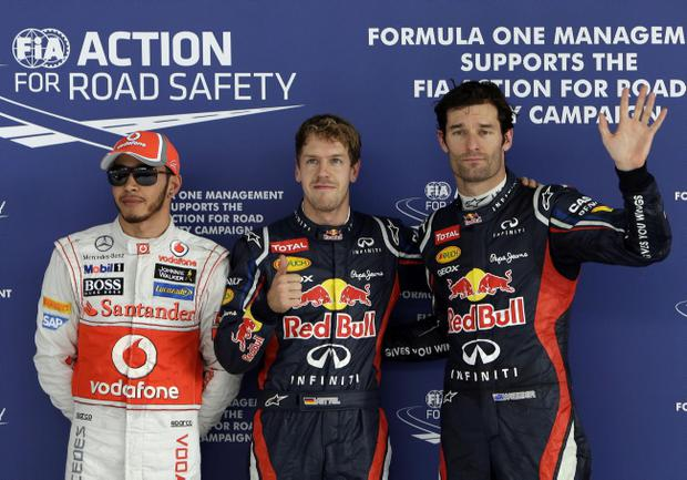 Red Bull driver Sebastian Vettel of Germany, center, poses for photos after taking pole position in the qualifying session for the Indian Formula One Grand Prix, at the Buddh International Circuit in Noida, on the outskirts of New Delhi, India, Saturday, Oct. 27, 2012. With him are second placed McLaren driver Lewis Hamilton of Britain, left, and third placed Red Bull driver Mark Webber of Australia. (AP Photo/Greg Baker)