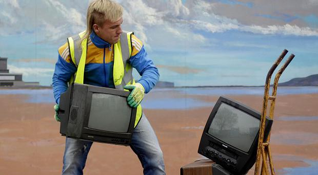 Andrew Lucasas - a worker at Ringsend Recycling Depot - wheels old TVs left by users before the digital switchover