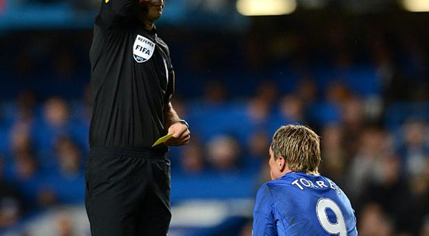 Chelsea's Fernando Torres is shown the red card and sent off by referee Mark Clattenburg for simulation during the Barclays Premier League match at Stamford Bridge, London