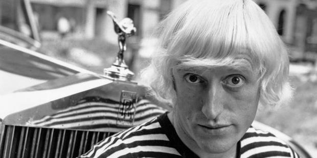 Jimmy Savile posing next to his Rolls-Royce car, 20th July 1964.