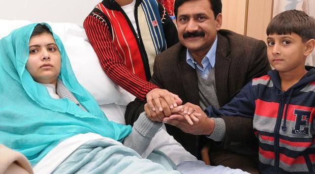 Malala Yousufzai in her Birmingham hospital bed surrounded by her family (Queen Elizabeth Hospital Birmingham/PA)