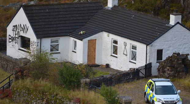Slogans painted on Alt-na-reigh, the Glencoe cottage owned by Jimmy Savile. On the left 'Jimmy the beast' and right a symbol showing a triangle with an eye above it resembling the 'Eye of Providence' used in Masonic imagery