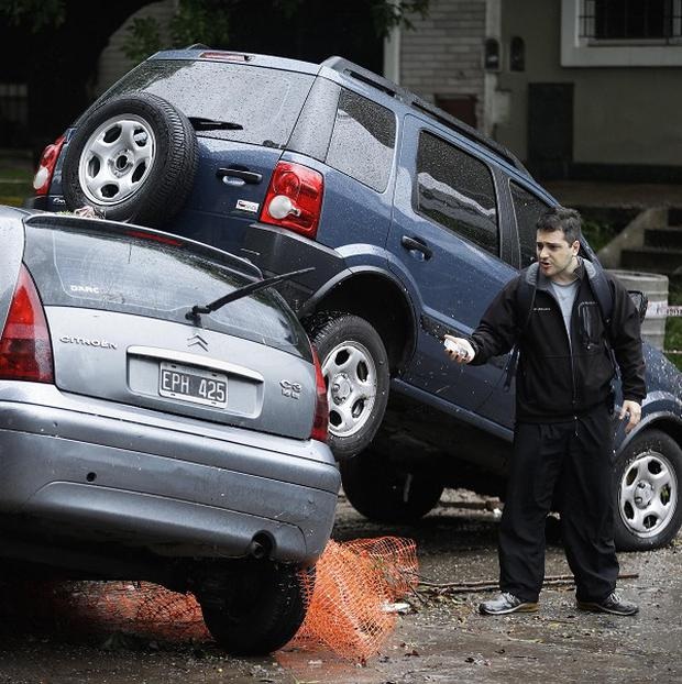 A man looks at damaged cars piled up by flash floods after heavy rains in Buenos Aires (AP)