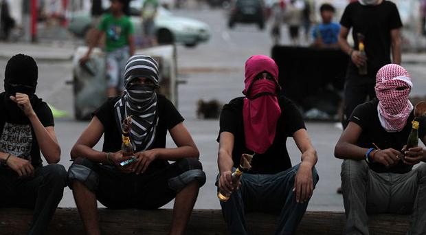 Masked anti-government protesters hold petrol bombs ahead of a march in Malkiya, Bahrain (AP)