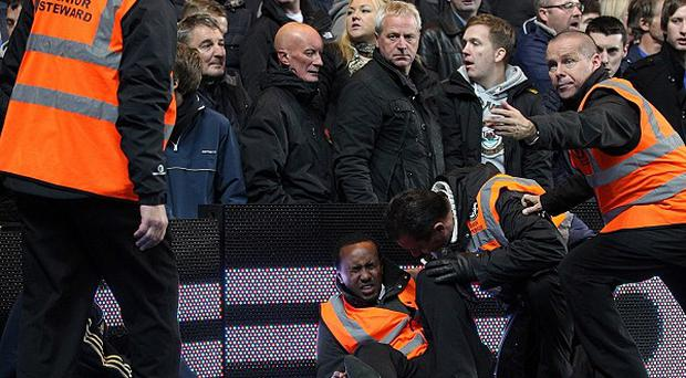 A steward lays injured on the floor following Manchester United's winner at Stamford Bridge