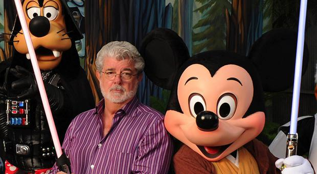 George Lucas poses with a group of 'Star Wars' inspired Disney characters