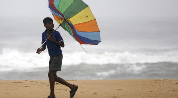 A boy struggles to hold on to his umbrella on India's Bay of Bengal coast (AP)