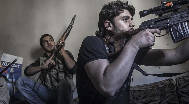 A rebel sniper takes aim in Aleppo (AP)
