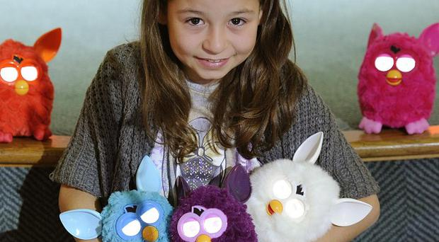 A fan poses with Furby toys at the Toy Retailers Association's Dream Toys exhibition