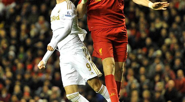 Swansea City's Miguel Michu (left) and Liverpool's Sebastian Coates (right) battle for the ball in the air during the Capital One Cup, Fourth Round match at Anfield, Liverpool. PRESS ASSOCIATION Photo. Picture date: Wednesday October 31, 2012. See PA story SOCCER Liverpool. Photo credit should read: Martin Rickett/PA Wire. RESTRICTIONS: Editorial use only. Maximum 45 images during a match. No video emulation or promotion as 'live'. No use in games, competitions, merchandise, betting or single club/player services. No use with unofficial audio, video, data, fixtures or club/league logos.