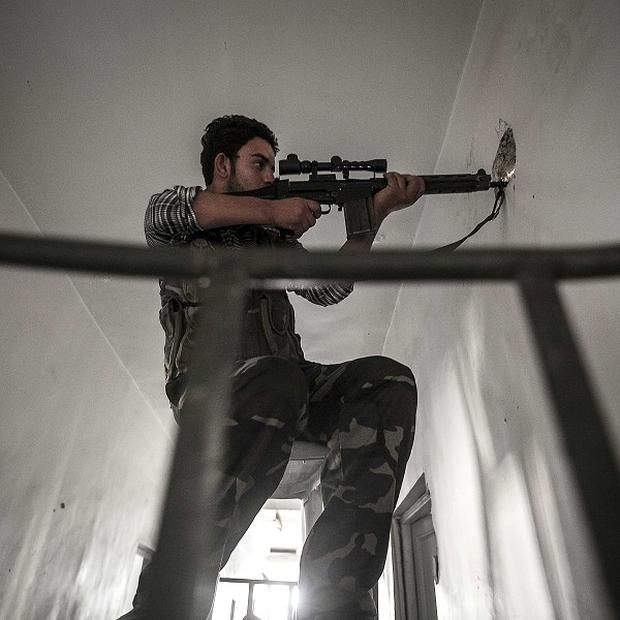 A rebel sniper keeps an eye on the enemy during skirmishes with the Syrian army (AP)