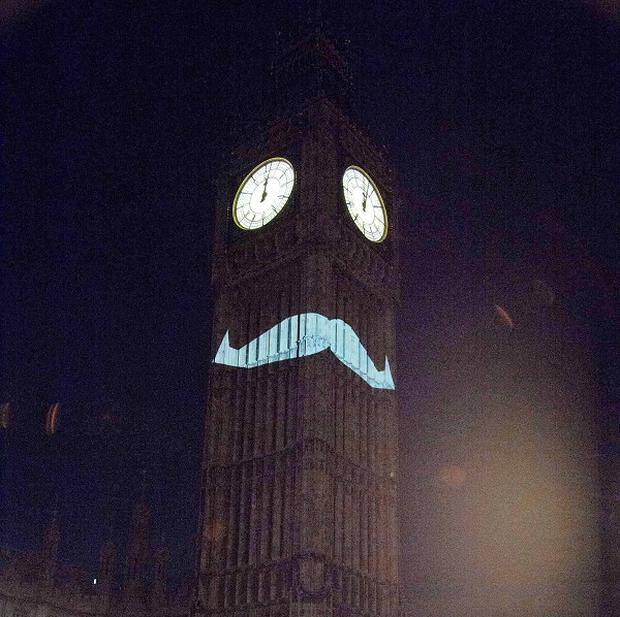A blue moustache is projected on to the side of Elizabeth Tower, which houses Big Ben, to promote Movember (Movember/PA)