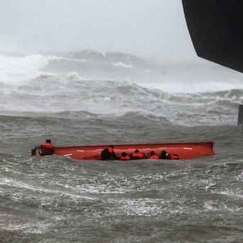 Sailors try to hold on to their up-turned lifeboat as others throw lines to them from the ship above (AP)