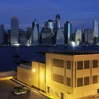 A Brooklyn building has electrical power but much of the lower Manhattan skyline, top, is without electricity after the storm (AP)