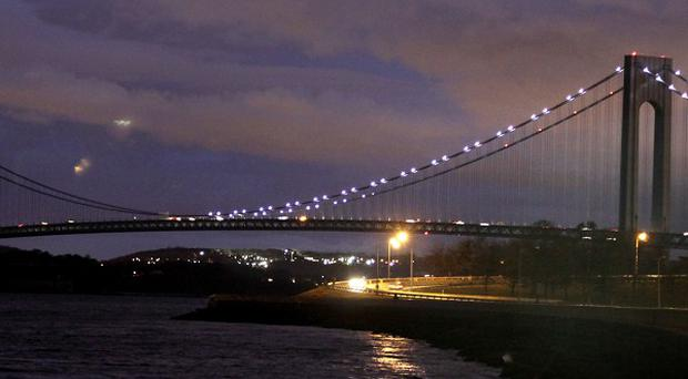 The half of the Verrazano Narrows Bridge attached to Brooklyn is lit while the half attached to Staten Island is dark in New York (AP)