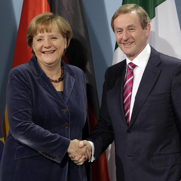 German chancellor Angela Merkel and Enda Kenny shake hands after a joint press conference (AP Photo/Michael Sohn)