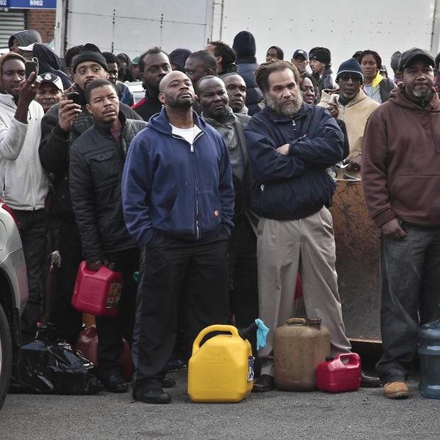 A crowd gathers at a service station with portable containers, waiting for petrol pumps to open in the Brooklyn borough of New York (AP)
