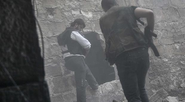 Rebel fighters in Syria run for cover through smoke from an explosion (AP)