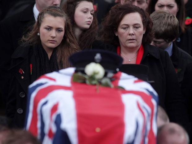 Northern Ireland- 6th November 2012 Mandatory Credit - Photo-Jonathan Porter/Presseye. Funeral of murdered prison officer David Black in Cookstown. Co. Tyrone. The father of two was shot dead on the M1 outside Lurgan on Thursday as he drove to work at Maghaberry Prison. Mr Black's coffin is carried from Molesworth Presbyterian Church after the funeral service followed by his daughter Kyra(left) and wife Yvonne.
