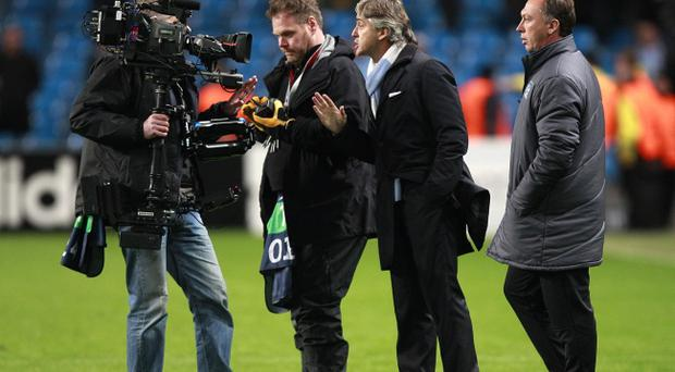 Manchester City manager Roberto Mancini (second right) is filmed by a TV cameraman as he complains about referee Peter Rasmussen after the final whistle during the UEFA Champions League match at the Etihad Stadium, Manchester