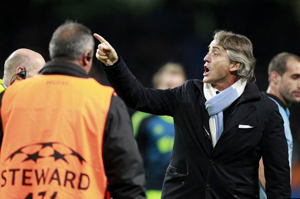 Manchester City manager Roberto Mancini (right) complains to referee Peter Rasmussen after the final whistle during the UEFA Champions League match at the Etihad Stadium, Manchester