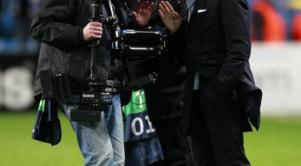 Manchester City manager Roberto Mancini (right) is filmed by a TV cameraman as he complains about referee Peter Rasmussen after the final whistle during the UEFA Champions League match at the Etihad Stadium, Manchester