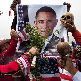 Peruvian shamans bless President Barack Obama using a poster of him during a ritual to predict the winner of the US presidential election (AP)
