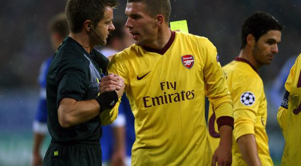 GELSENKIRCHEN, GERMANY - NOVEMBER 06: (L-R) Referee Nicola Rizzoli of Italy talks with Lukas Podolski of Arsenal during the UEFA Champions League group B match between FC Schalke 04 and Arsenal FC at Veltins Arena on November 6, 2012 in Gelsenkirchen, Germany. (Photo by Christof Koepsel/Bongarts/Getty Images)