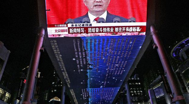A huge screen shows a broadcast of Chinese President Hu Jintao speaking at the opening session of the Congress in Beijing (AP)