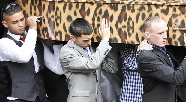 The pallbearers carry the leopard skin-style coffin containing Karina Menzies