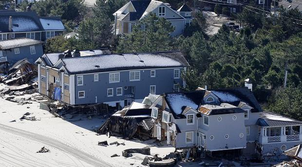 People stand near damaged homes in New Jersey after the region was pounded by Superstorm Sandy last week (AP Photo)