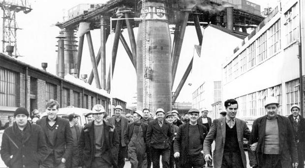 Harland & Wolff shipyard workers finish for the day as the truly massive Sea Quest dominates the sky-line. 14/1/1966