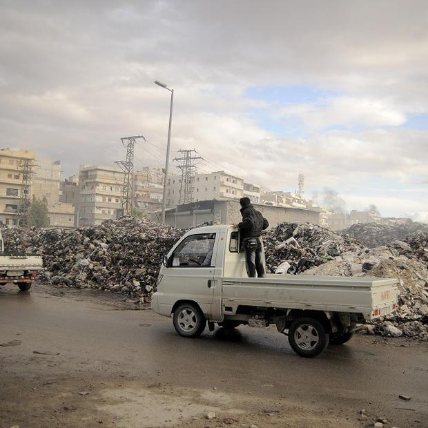 Trucks pass a mountain of garbage in Aleppo, where there has been heavy fighting and shelling between the Syrian Government and rebels (AP)