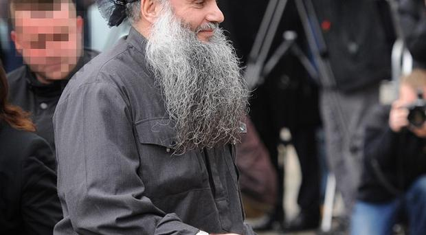 Terror suspect Abu Qatada arrives at his London home after leaving prison following his victory in the latest round in his battle against deportation