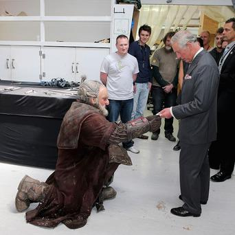 The Prince of Wales is handed a birthday card as he meets Mark Hadlow who plays Dori in the new Hobbit film in New Zealand