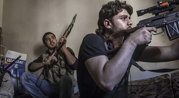 A rebel sniper aims at Syrian army positions in the Jedida district of Aleppo, Syria (AP)