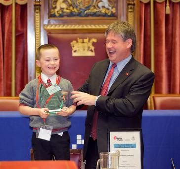 Overall winner Conor Heavron from Woodlands Language Unit takes the stage with Basil McCrea, MLA to tell his winning joke.