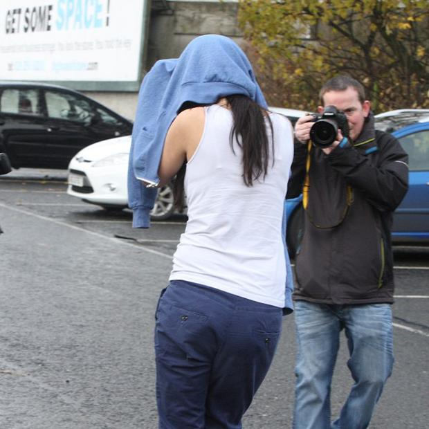 Jennifer Toland, 23, hides her face as she leaves Ballymena Magistrates' Court charged with the manslaughter of Bertie Acheson