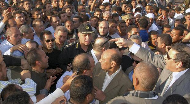Egyptians confront authorities who arrived at the scene of a train crash that killed around 50 people (AP)