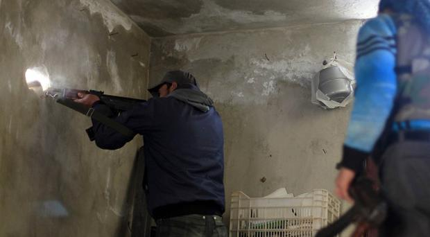 A fighter shoots his weapon through a hole in the wall during clashes with Syrian army forces (AP)