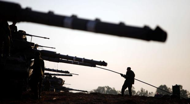 Israeli soldiers tend to their tanks in a deployment area on Israel's border with the Gaza Strip, on November 18, 2012