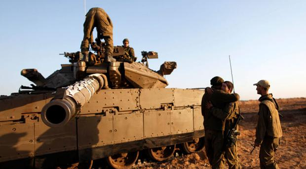 Israeli soldiers stand on and around their tanks in a deployment area on Israel's border with the Gaza Strip, on November 18, 2012
