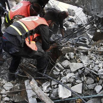 Palestinians sift through the rubble of a family house following an Israeli airstrike in Gaza City (AP)