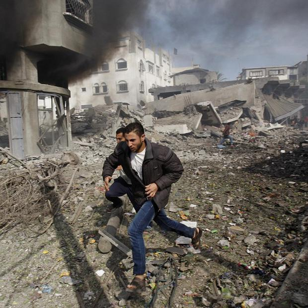 Palestinians run away from a damaged building after an Israeli airstrike in Gaza City (AP)