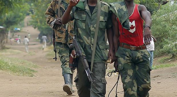 M23 rebel fighters walk through the streets of Kiwanja, 50 miles north of Goma, DR Congo (AP)