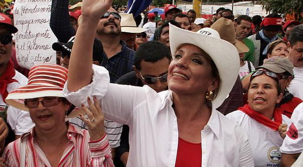 Xiomara Castro Zelaya, right, wife of former Honduras president Manuel Zelaya, waves to supporters (AP)