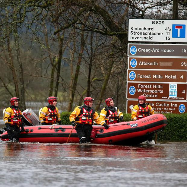 Firemen wade through Aberfoyle after the town was flooded when the River Forth burst its banks.
