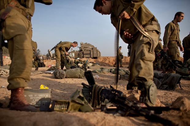 ISRAEL/GAZA BORDER, ISRAEL- NOVEMBER 19: (ISRAEL OUT) Israeli soldiers prepare weapons in a deployment area on November 19, 2012 on Israel's border with the Gaza Strip. The death toll has risen to at least 85 killed in the air strikes, according to hospital officials, on day six since the launch of operation 'Pillar of Defence.' (Photo by Uriel Sinai/Getty Images)