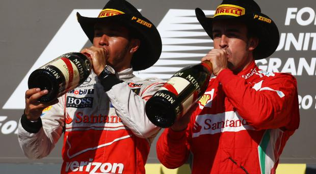 AUSTIN, TX - NOVEMBER 18: Race winner Lewis Hamilton (L) of Great Britain and McLaren celebrates on the podium with third placed Fernando Alonso (R) of Spain and Ferrari following the United States Formula One Grand Prix at the Circuit of the Americas on November 18, 2012 in Austin, Texas. (Photo by Paul Gilham/Getty Images)