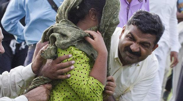 A Pakistani police officer and a volunteer escort a young Christian girl accused of blasphemy away from a prison in Rawalpindi, Pakistan (AP)